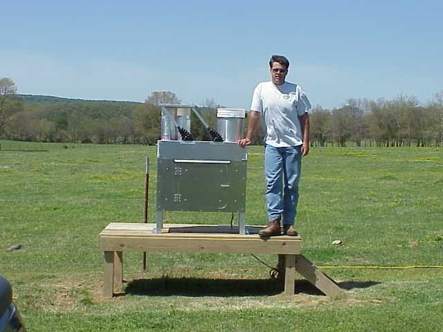 Man standing next to air monitoring equipment. Grass and wide open space in background