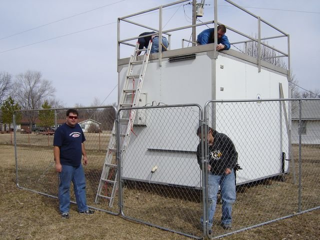 Four people interacting with air monitoring equipment outside