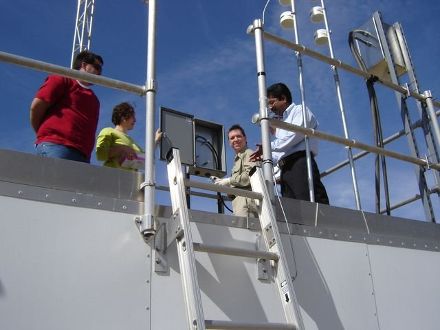 Four people gathered around air monitoring equipment