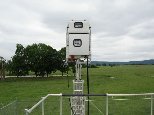 Air monitoring equipment with grass and trees in background