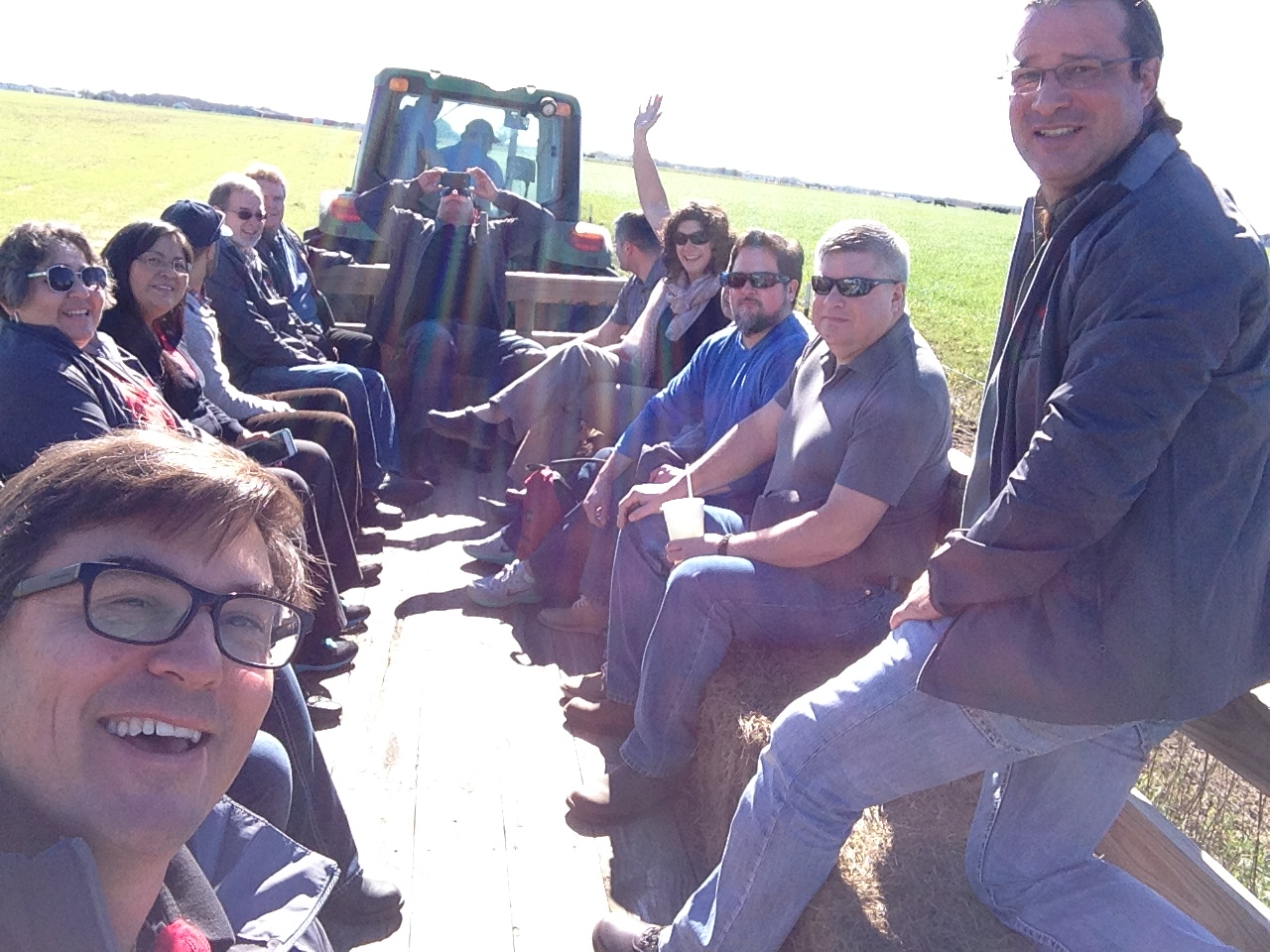 NTAA Members on a wagon being pulled by a tractor in a field