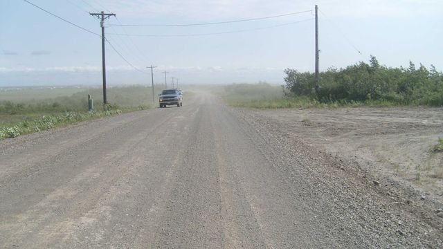 View of dirt road, truck in distance