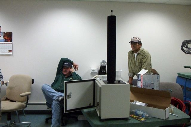 Two men in a room next to equipment
