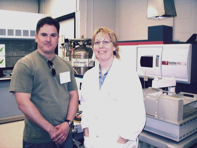 Man in lab standing next to woman in a lab coat smiling at camera