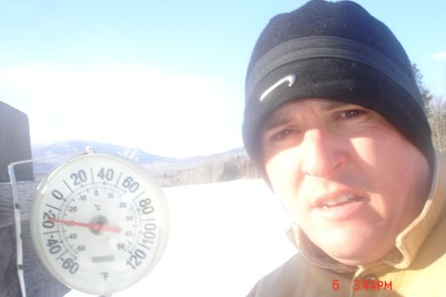 Man standing outside looking at camera beside a thermometer showing -20 degrees fahrenheit