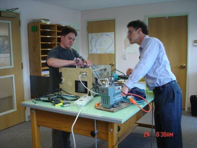 Two men in a room interacting with air monitoring equipment