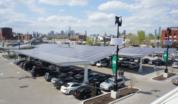 a parking lot with solar panels shading the cars